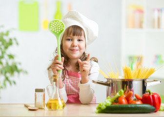 Kid cook makes healthy vegetables meal in the kitchen