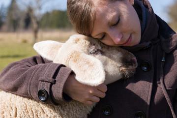 hübsche Frau umarmt innig ein kleines Lamm