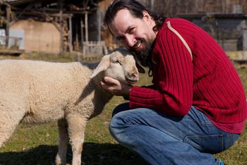 Attraktiver Mann umarmt ein süsses Lamm