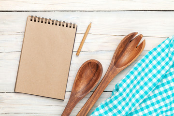 Notepad over kitchen towel and utensils on wooden table