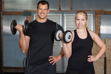 Cross fit - couple in a gym doing exercise with barbell