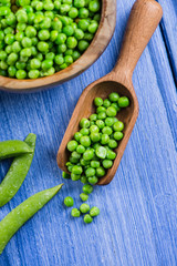 Wooden scoop with fresh peas on blue table