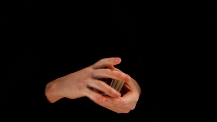 Magician playing card trick on black background
