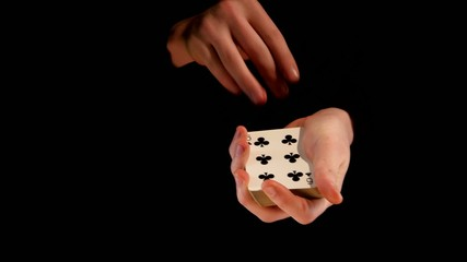 Magician shows his trick with cards on black background