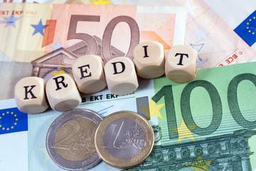 Geld und Holzwürfel mit dem Wort Kredit