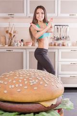 healthy girl fighting against hamburger