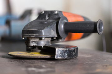 Close-up of angle grinder lying on table