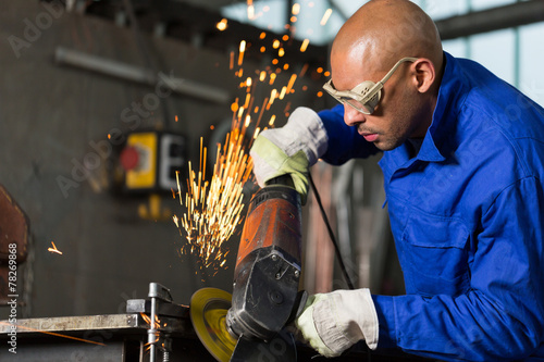worker grinding metal with angle gringer - 78269868
