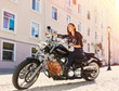 Biker girl in a leather jacket riding a motorcycle - 78270896