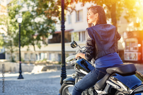 Leinwandbild Motiv Biker girl in a leather jacket on a motorcycle