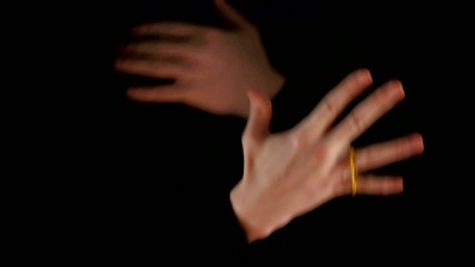 Magician making performance with elastic on black background