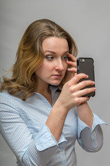 Business Woman fixing eye make up in the cell phone camera