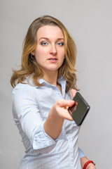 Business Woman Passing a cell phone to the camera