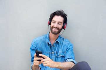 Handsome young man smiling with cellphone and headphones