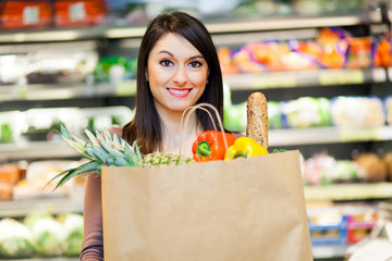 Woman holding a paper shopping bag full of fruit and vegetables