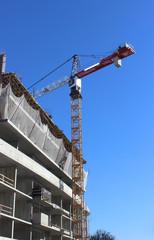 башенный кран строит дом