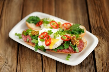 Poached egg sandwiches with chili, scallion and salami selective