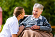 Pflegerin hält Hand alter Frau im Rollstuhl - 78275065