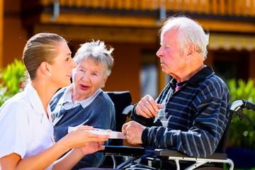 Senioren im Garten von Altersheim essen Pralinen