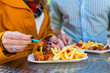 canvas print picture - Paar isst Currywurst an Imbissbude