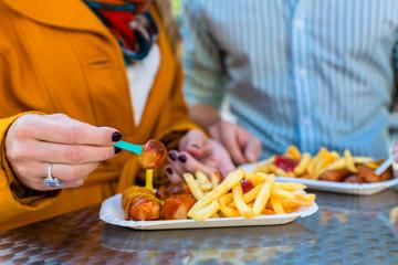 Paar isst Currywurst an Imbissbude