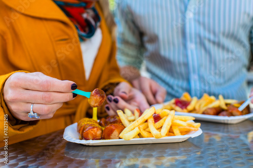canvas print picture Paar isst Currywurst an Imbissbude