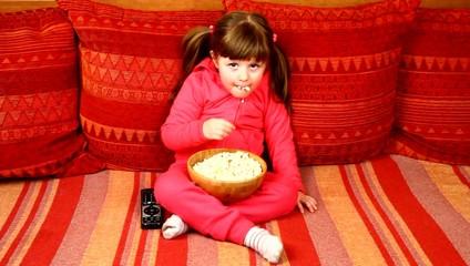 little girl eating popcorn in front of tv