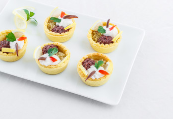 Salty mini tarts stuffed with green and black olive paste