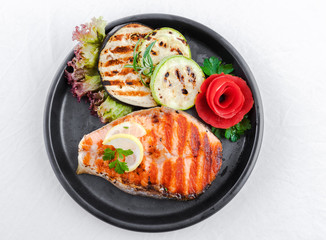 Grilled salmon, sliced zucchini and courgette, lettuce and lemon