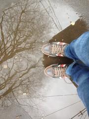 con i piedi dentro l'acqua di una pozzanghera