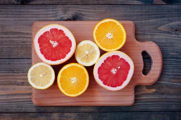 Fresh citrus on color wooden background