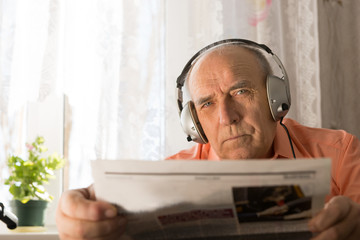 Serious Old Age Man with Headset Holding Newspaper