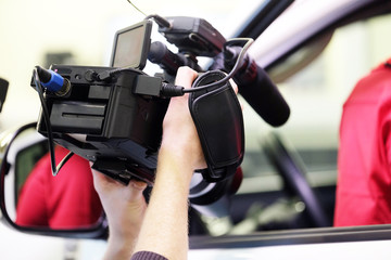 The image of hands holding a professional camcorder