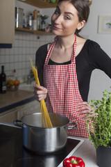 Frau beim Kochen von Spaghetti in der Küche