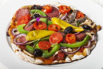 Pizza mit allem auf einem Teller