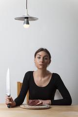 Frau mit einem Kochmesser und Fleisch