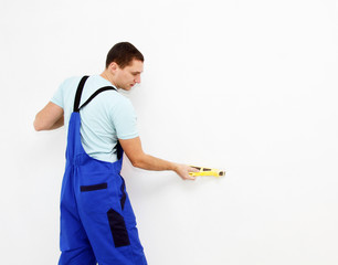 Male plasterer in uniform polishing the wall