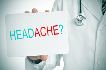 doctor showing a signboard with the question headache?