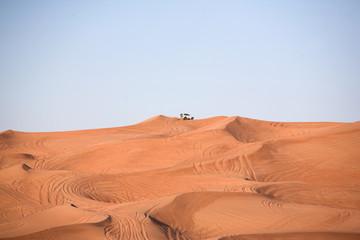 Desert dunes, an off-road car alone