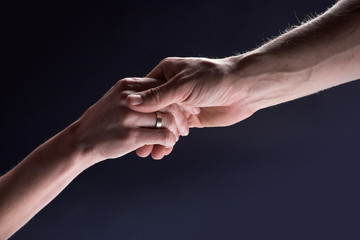 Helping male hand holds hand of a woman