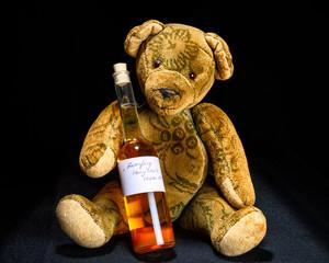 Antiker Teddy sitzt mit einem Fläschchen Honiglikör auf Schwarz