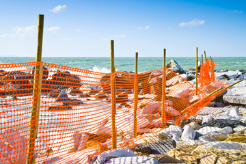 Construction site with safety orange grid at the seaside