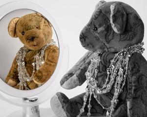 Antiker Teddy mit Schmuck betrachtet sich im Spiegel