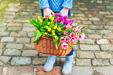 A big basket full of fresh colorful tulips holding by a child
