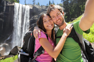 Hikers couple taking selfie at Yosemite waterfall