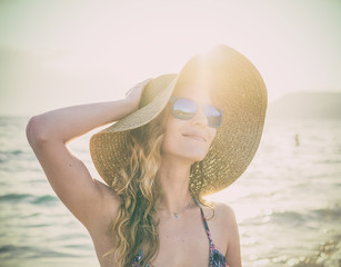 Young blondy girl in sunglasses and straw hat at the beach