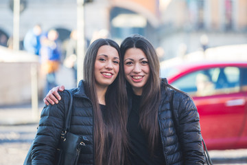Female Twins Portrait in the City with Traffic on Background.