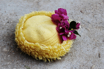yellow hat and paper flower on the floor