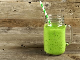 Healthy green smoothie in a mason jar mug on old wood