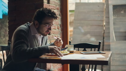 Young businessman working with a tablet while is eating a